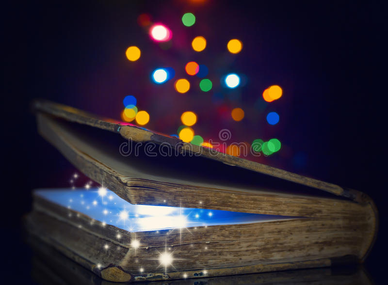 Old magic book. Colored lights garland stock images