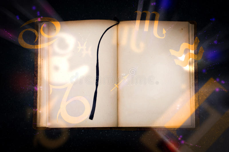 Old magic book with glowing zodiac symbols. Empty page for your text royalty free stock photos