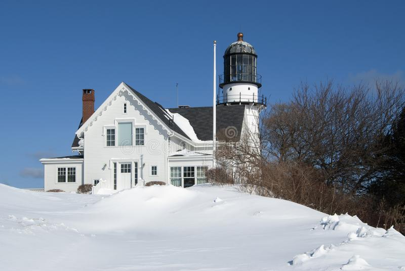 Old Maine Lighthouse Covered in Snow from New England Storm. Cape Elizabeth lighthouse, with its old worn tower is surrounded by snow drifts from a passing New stock photography