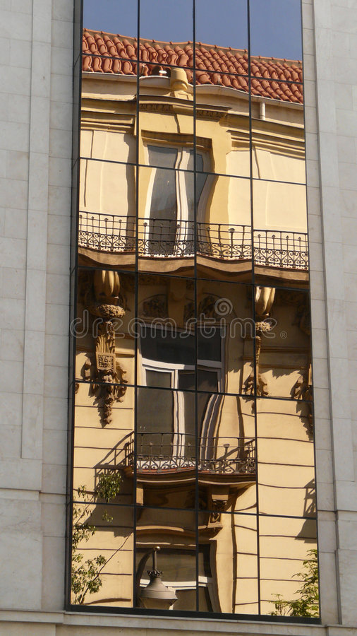 Old Malaga's building mirroring. Old building mirroring in the glass windows of a modern building royalty free stock photos