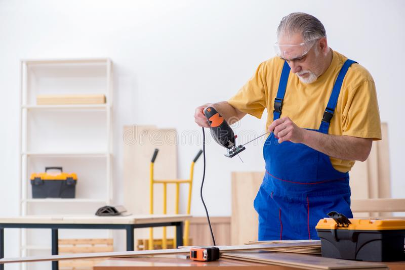 Old male carpenter working in workshop. The old male carpenter working in workshop royalty free stock photography