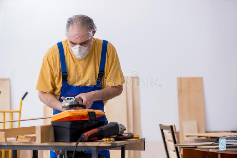 Old male carpenter working in workshop. The old male carpenter working in workshop stock photos