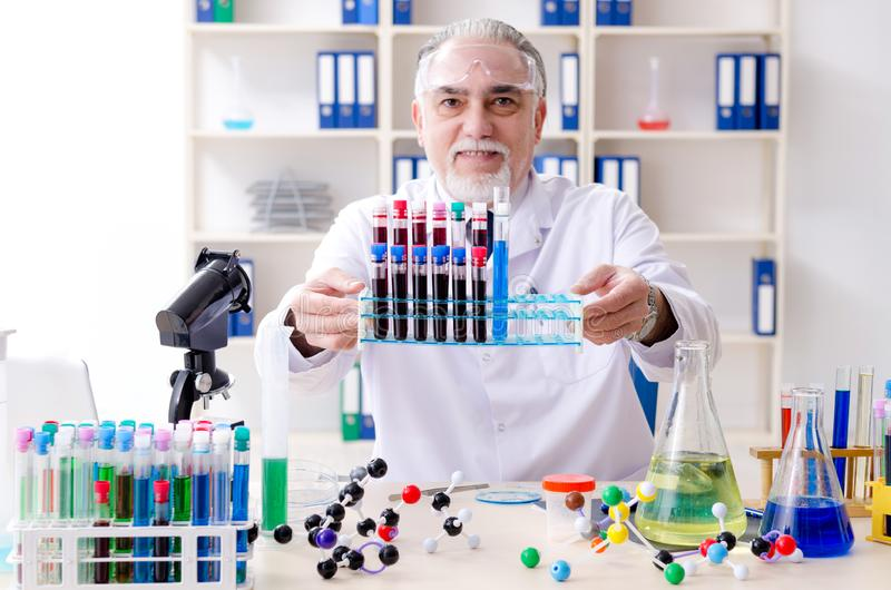 The old male chemist working in the lab. Old male chemist working in the lab royalty free stock photo