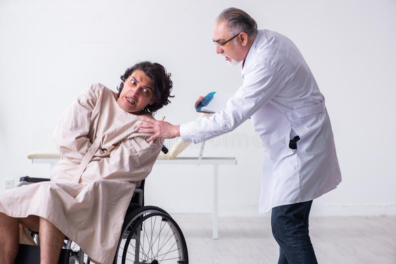 Old male doctor psychiatrist and patient in wheel-chair. The old male doctor psychiatrist and patient in wheel-chair stock photography