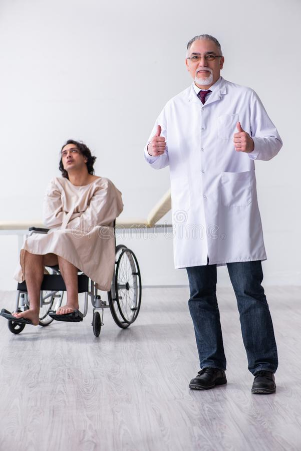 Old male doctor psychiatrist and patient in wheel-chair. The old male doctor psychiatrist and patient in wheel-chair royalty free stock photo