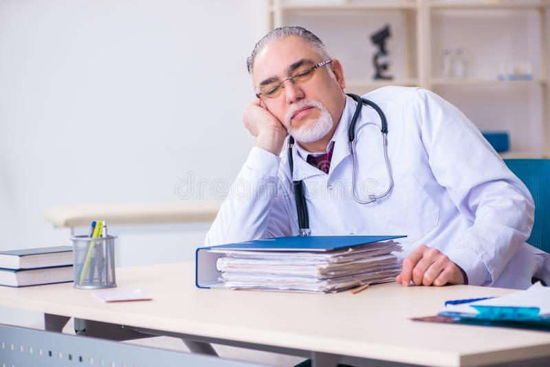 Old male doctor working in the clinic. The old male doctor working in the clinic royalty free stock photo