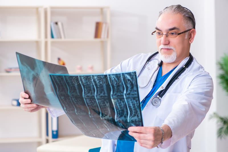 Old male doctor working in the clinic. The old male doctor working in the clinic royalty free stock photography