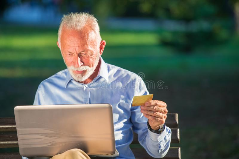 Old male sitting on bench and surfing net on laptop in park, shopping online concept.  royalty free stock photo