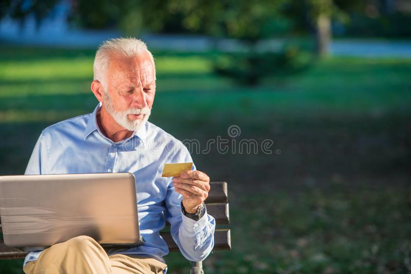 Old male sitting on bench and surfing net on laptop in park, shopping online concept.  stock image