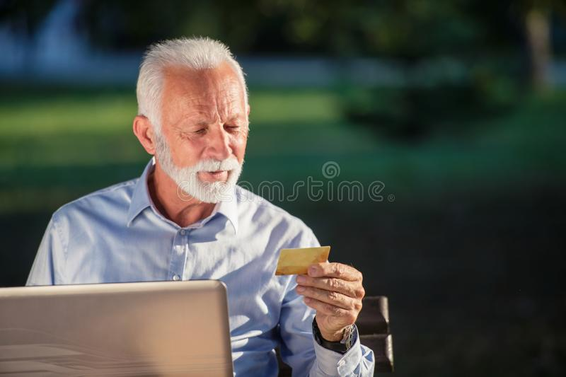 Old male sitting on bench and surfing net on laptop in park, shopping online concept.  royalty free stock images