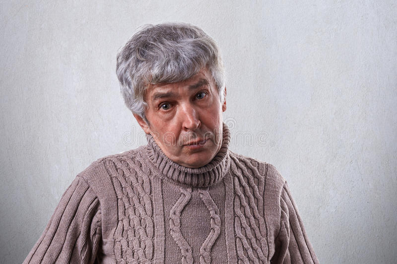 An old male with wrinkles having gray hair dressed in sweater having sympathetic expression isolated over white background. Mature. Man posing in studio. People royalty free stock photo