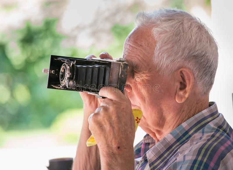 Old man with analog camera. Senior man taking photos with old analog camera in park stock photography