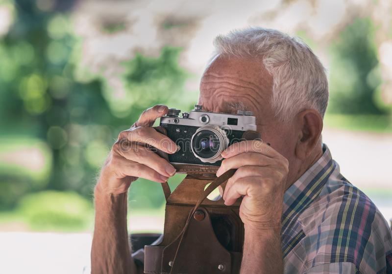 Old man with analog camera. Senior man taking photos with old analog camera in park royalty free stock image