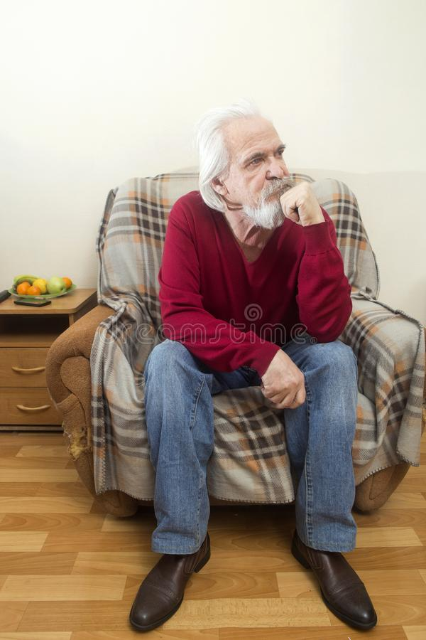The old man in the armchair at home royalty free stock images