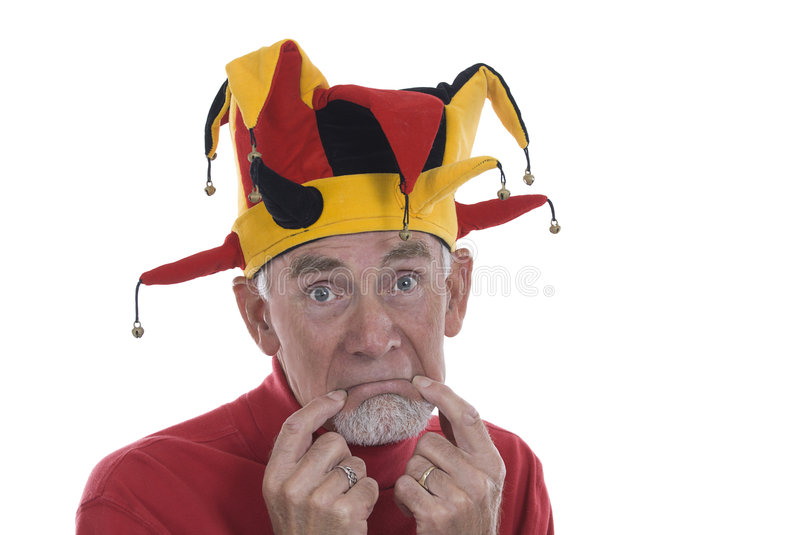 Old man as clown in jester's hat royalty free stock photography