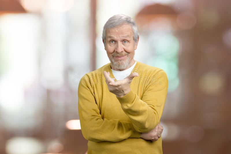 Old man asking a question what is it. Portrait of arrogant grandfather is criticizing. Abstract blurred background stock photos