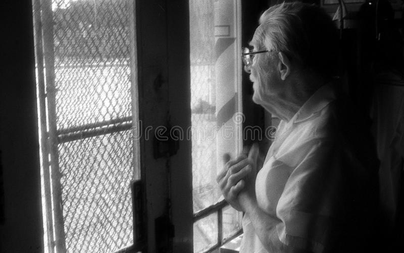 St Louis, Missouri, United States-circa 2007-Old Man Barber Staring Out Vintage Barbershop Window in City Neighborhood stock photos
