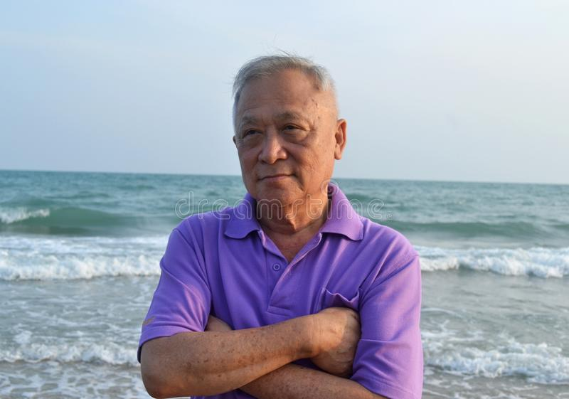 Old man on the beach. Asian old man on the beach stock photo