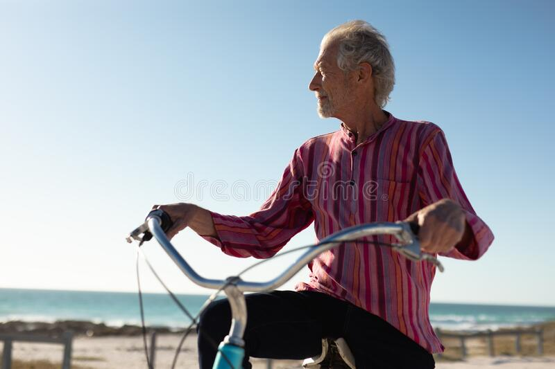 Old man with a bike at the beach. Front view close up of a senior Caucasian man at the beach in the sun, sitting on a bicycle and looking away, the sea and blue stock photos