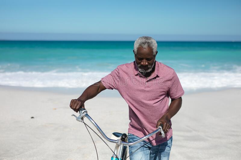Old man with a bike at the beach. Front view of a senior African American man wheeling a bike on the beach with blue sky and sea in the background royalty free stock photos