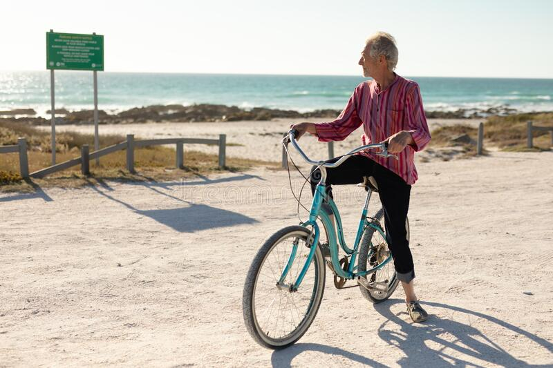 Old man with a bike at the beach. Front view of a senior Caucasian man at the beach in the sun, sitting on a bicycle and looking away, the sea in the background stock photography