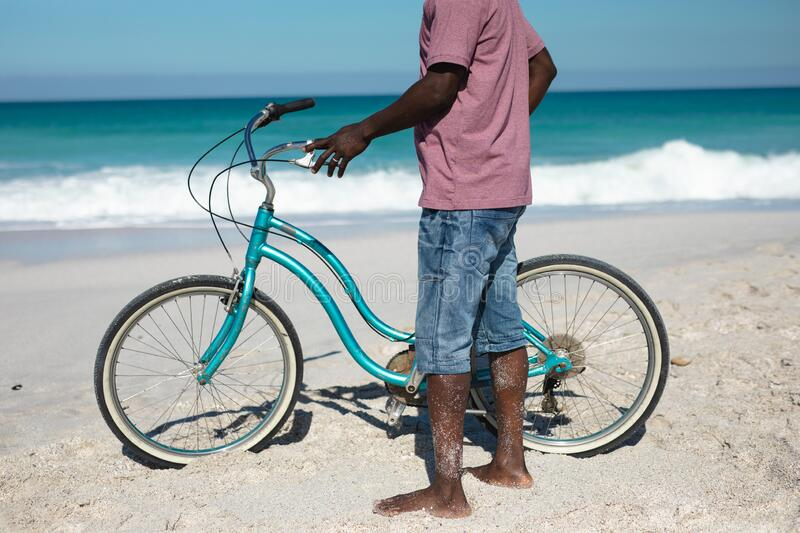 Old man with a bike at the beach. Low section of a senior African American man standing barefoot on the beach with blue sky and sea in the background, holding a stock photography