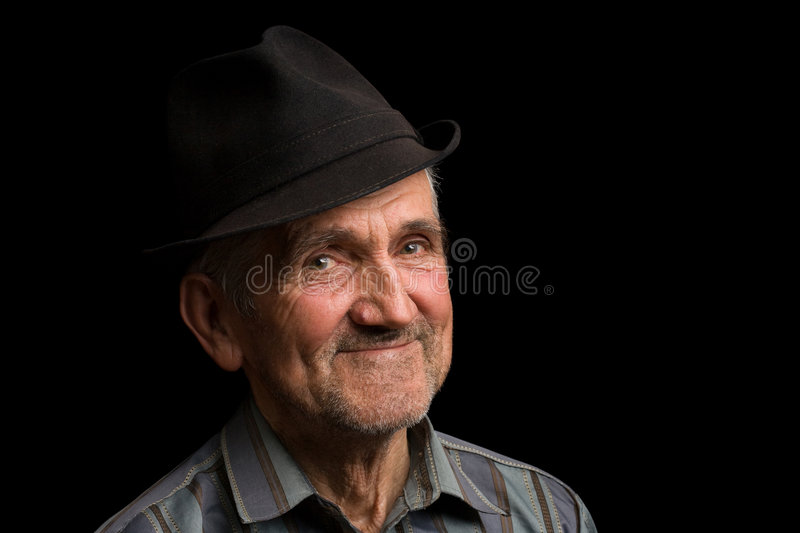 Old man with black hat. Portrait of a happy old man with hat, isolated on black