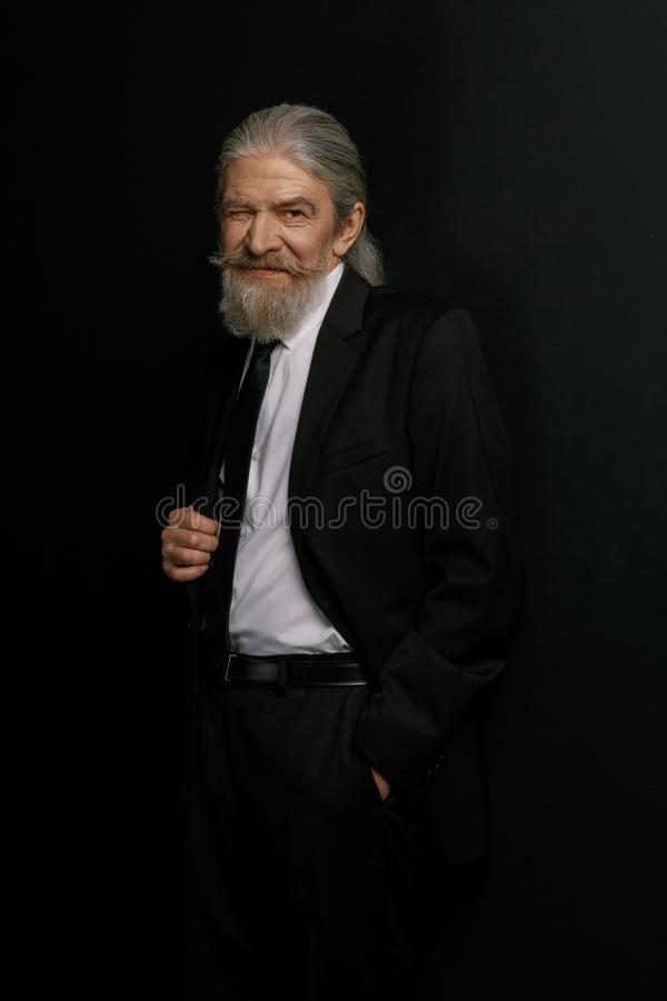 Old man in black suit and white shirt standing against black background. royalty free stock photo