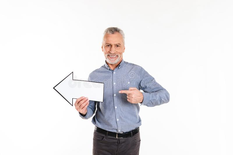 Old man in blue shirt pointing and holding arrow left isolated. Old cheerful man in blue shirt pointing and holding arrow left and smiling isolated over white stock photos