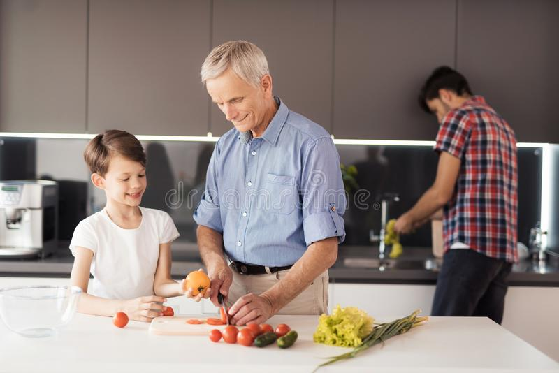 The old man and the boy are cutting tomatoes to make a salad for Thanksgiving. Behind them, a man washes salad leaves. An old men in a blue shirt is throwing royalty free stock photo