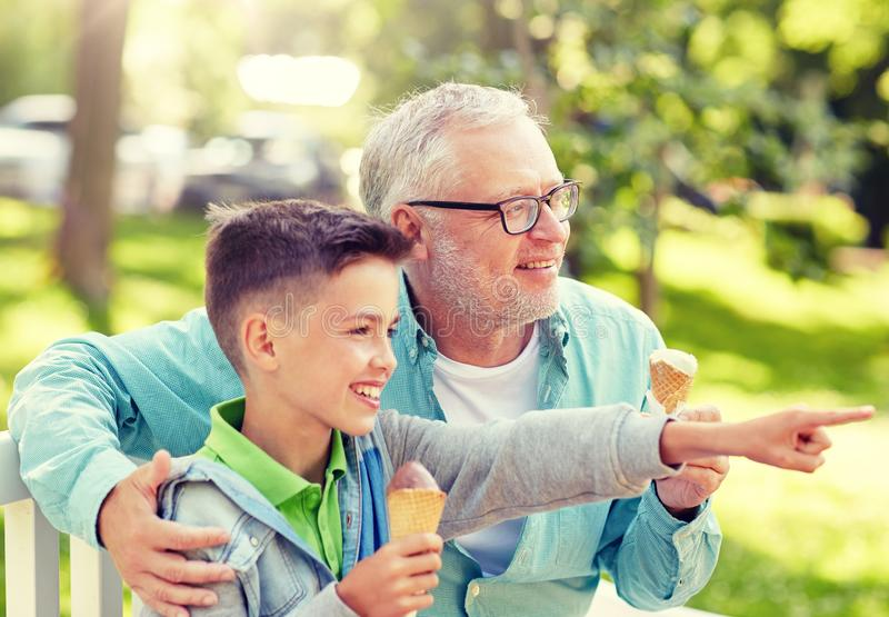 Old man and boy eating ice cream at summer park stock image
