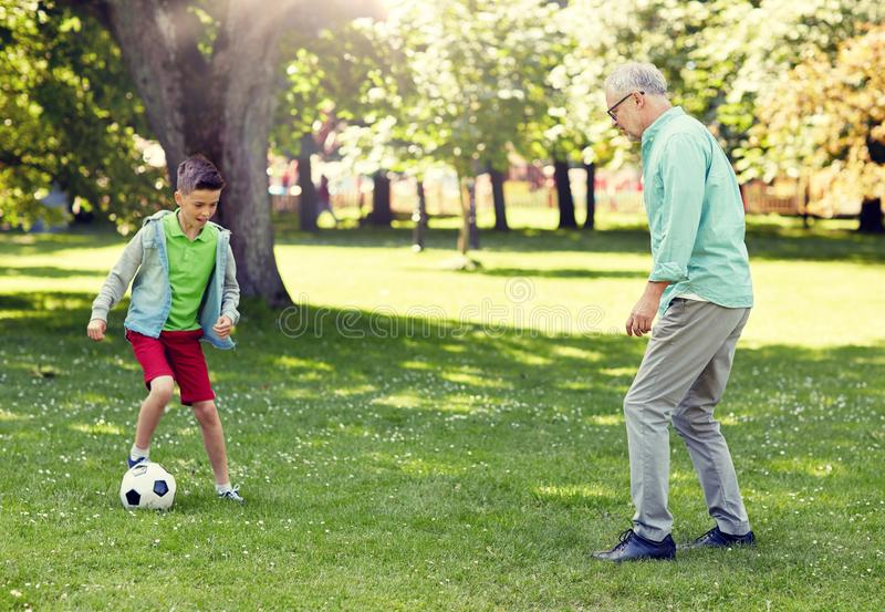 Old man and boy playing football at summer park royalty free stock photo