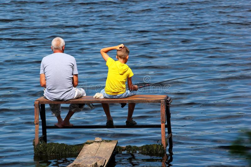 Old man and a boy sit on a self-made fishing platform with rods stock photos