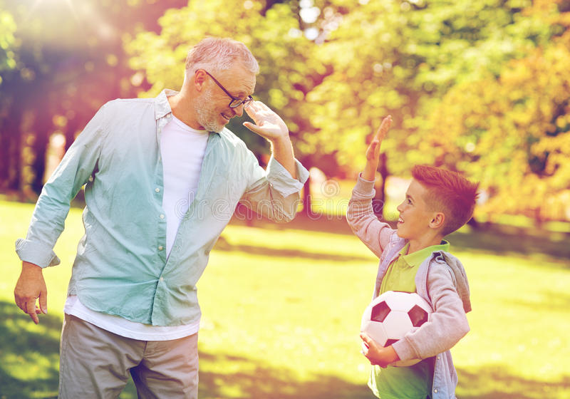 Old man and boy with soccer ball making high five stock photos
