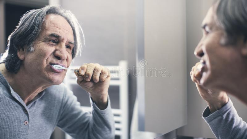 Old man brushing teeth in front of the mirror. Old man brushing teeth in front of the  mirror royalty free stock photos