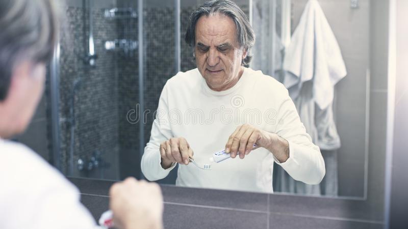 Old man brushing teeth in front of the mirror. Old man brushing teeth in front of the  mirror stock photography