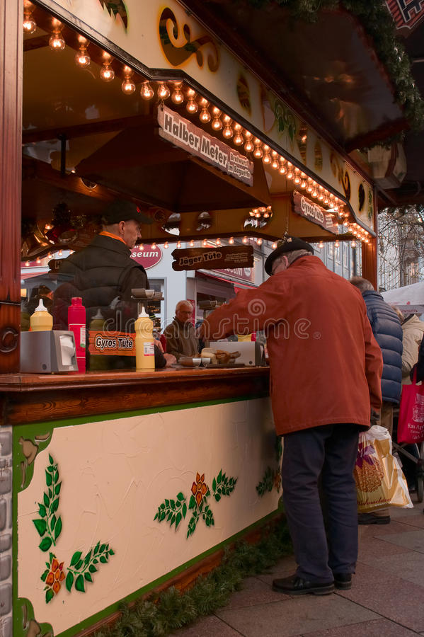 An old man buying some food on a Christmas market in Goettingen, Germany stock photos