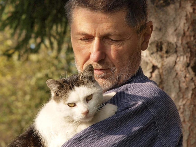 Old man with a cat. An old man with a beard wearing work clothes caressing the white-black stained cat in the nature environment stock photography