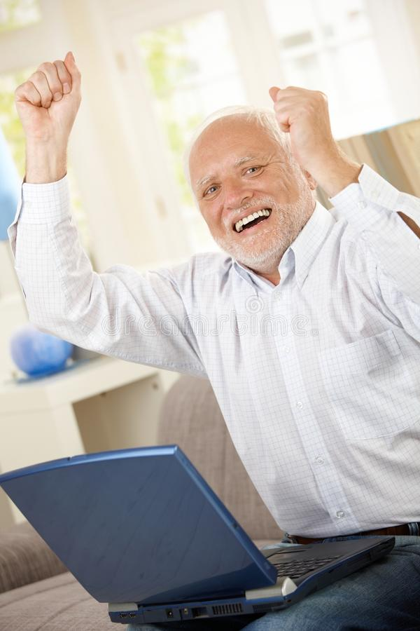 Old man celebrating with laptop. Old man celebrating at home, laughing and raising arms, having laptop computer, looking at camera