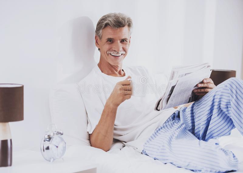 Old Man with Cup of Coffee Reading Newspaper. royalty free stock photography