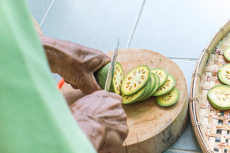 Old man cutting Bale fruit on wooden chopping block stock photography