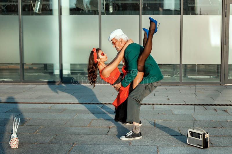 Old man dancing with a young girl. royalty free stock photo