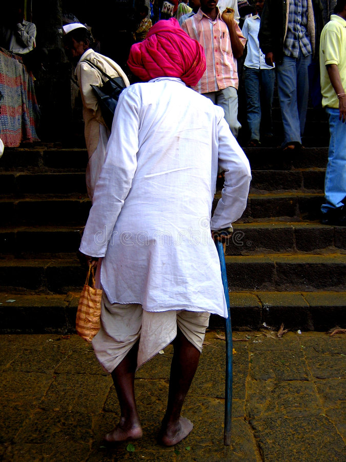 Old Man Devotion. On the great Khandoba festival day, an old man walks up the stairs leading to the temple. The great Khandoba festival is celebrated on the royalty free stock image
