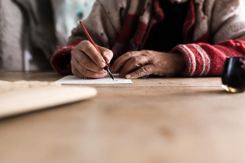 Old man with dirty hands writing a letter using a nib pen and in. K or pigment from a pot in a low angle view across a wooden table royalty free stock image