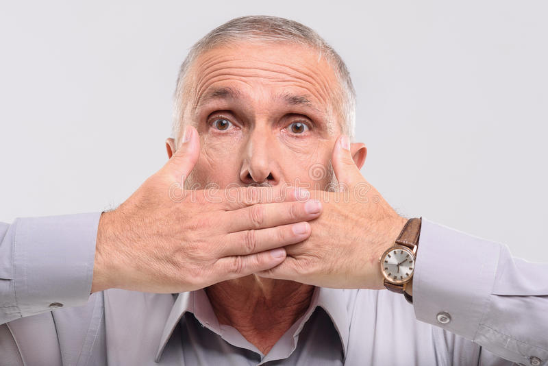 Old man does not want to talk. Keep quiet, elderly male covering his mouth with hands stock image