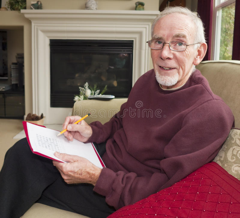 Download Old man doing word puzzle stock photo. Image of retired - 13363596