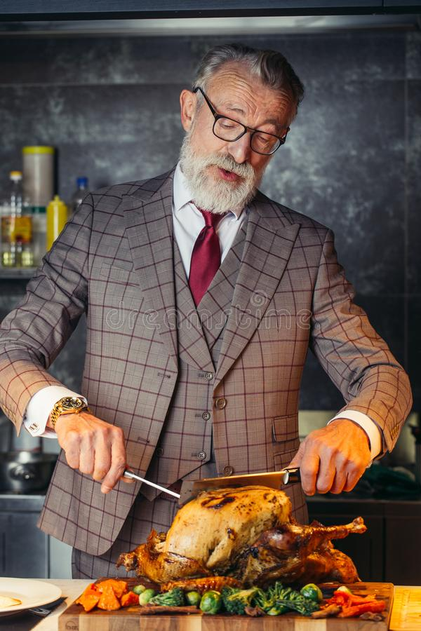 Old-aged handsome man in formal expensive suit cutting out roasted chicken stock photo