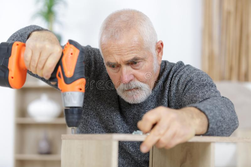 Old man drilling wood furniture at home. Man stock images