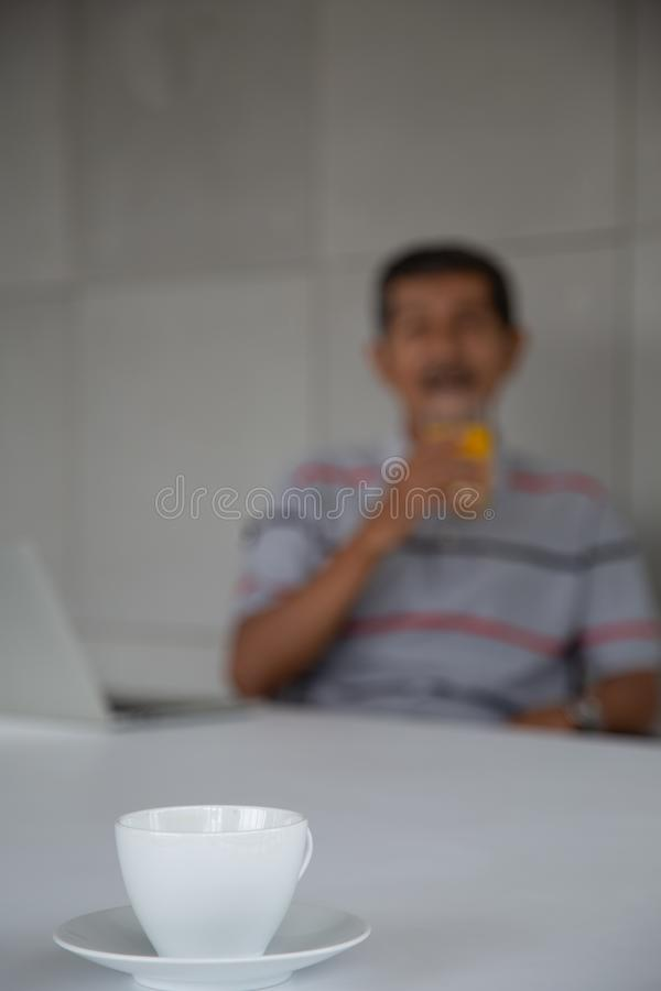 Old man drink orange juice for healthy in his work room stock images