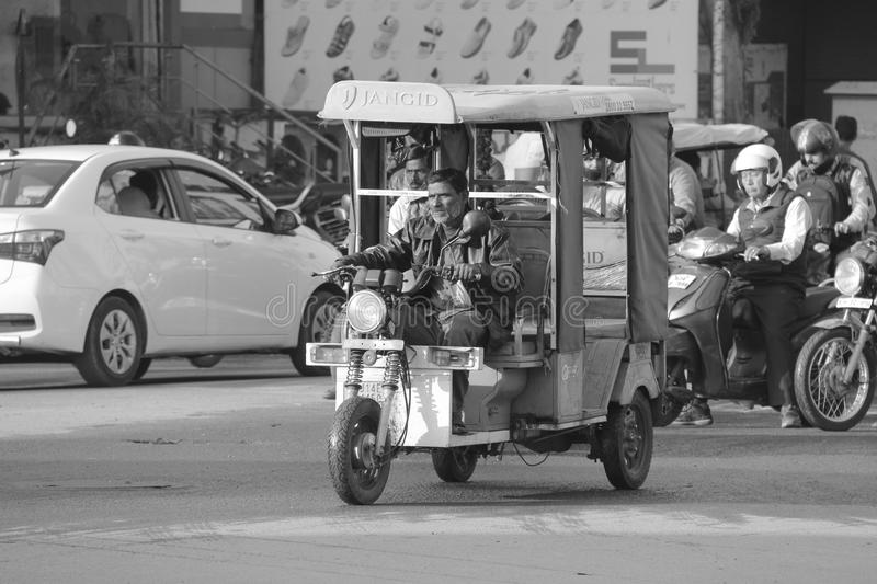 Old man drives tuk tuk car in India. Tuk Tuk, also known as auto rickshaw in India is driven by old drive in the main streets of India. This is a very popular royalty free stock image